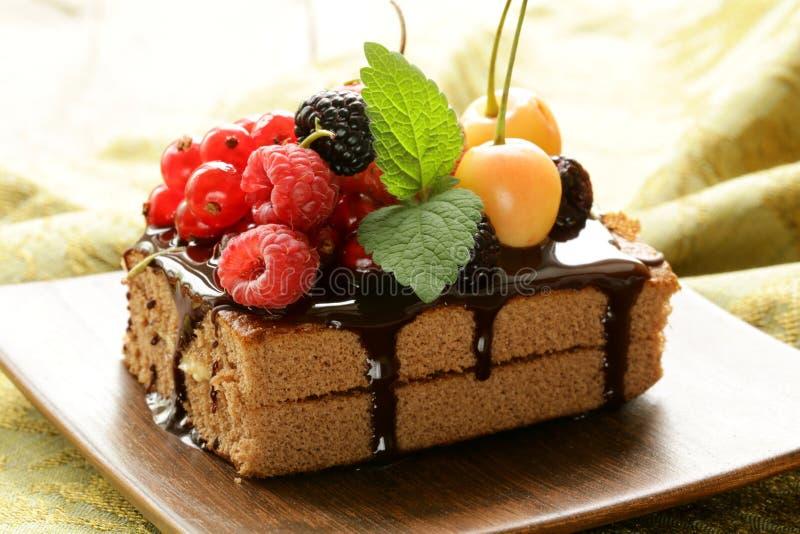 Chokladkaka med bär (hallon, vinbär, körsbäret) arkivfoto