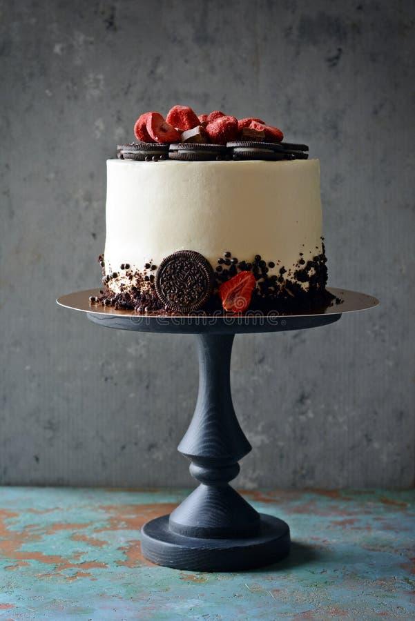 Chokladkaka med gräddostfyllning- och Oreo chokladkakor med frystorkade jordgubbar på en mörk bakgrund arkivbild