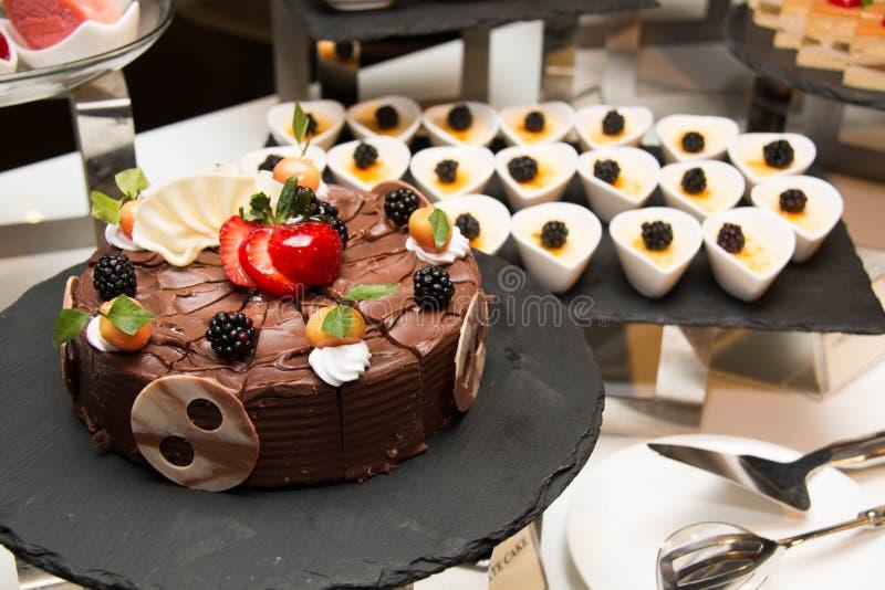 Chokladkaka med jordgubbar på den bruna plattan arkivfoton