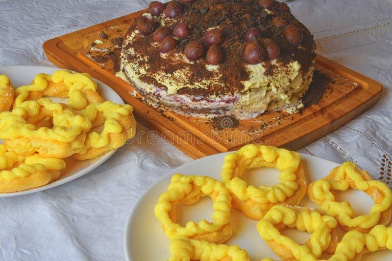 Chokladkaka med körsbär, grated choklad och piskad kräm Hemlagad kräm pusta på den festliga tabellen arkivbild