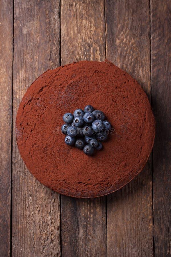 Chokladkaka med kakaopulver och blåbär arkivfoto