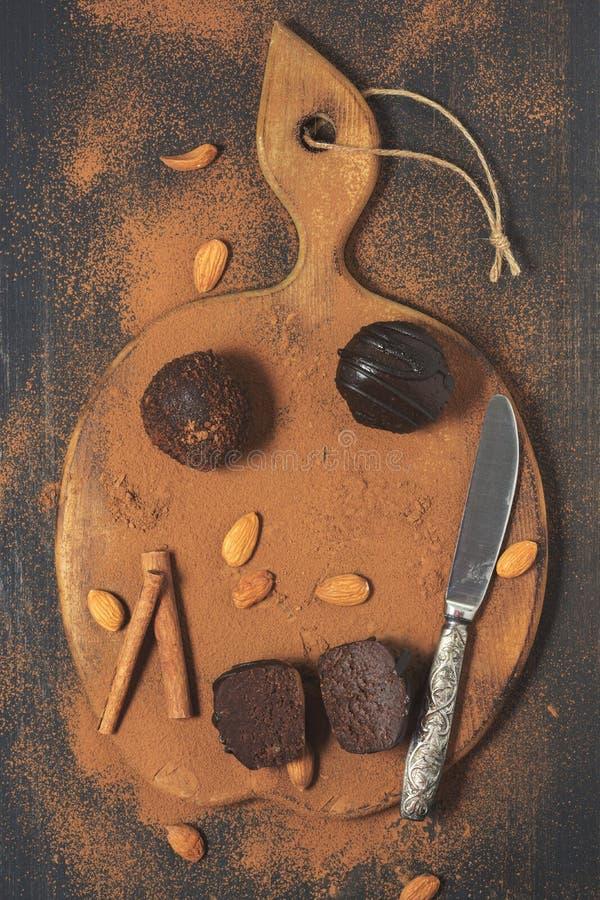 Chokladkaka med kakaopulver på en träskärbräda arkivbilder
