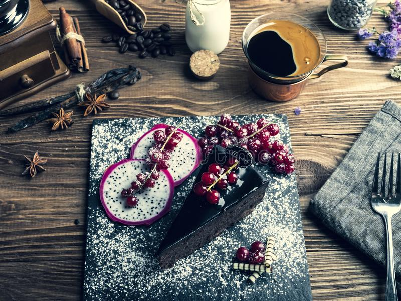 Chokladkaka mozart, röd vinbär på tabellen en kopp kaffe, kräm royaltyfri bild
