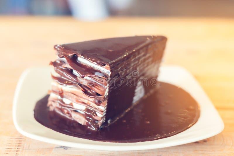 Chokladkaka på den vita maträtt- och trätabellen i coffee shop fotografering för bildbyråer