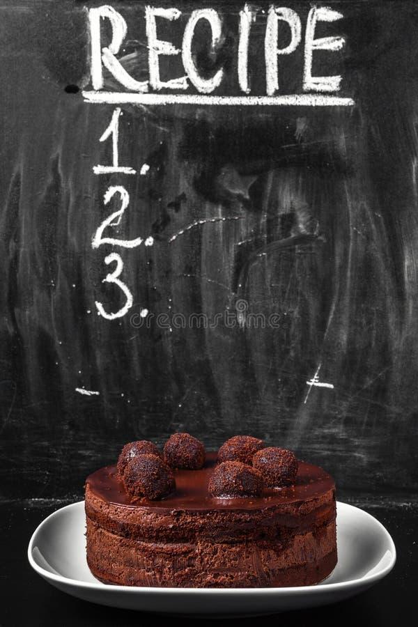 Chokladkaka på en vit porslinmaträtt på bakgrunden av en kritisera med inskriftreceptet och objekt för påfyllning royaltyfri foto