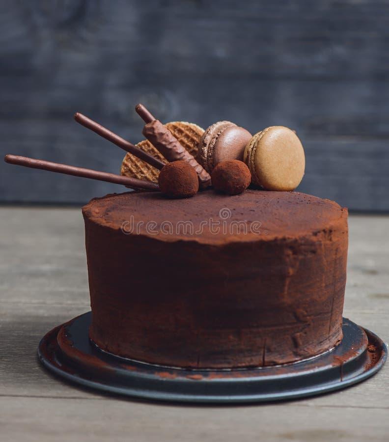Chokladkaka på svart ställning arkivbild