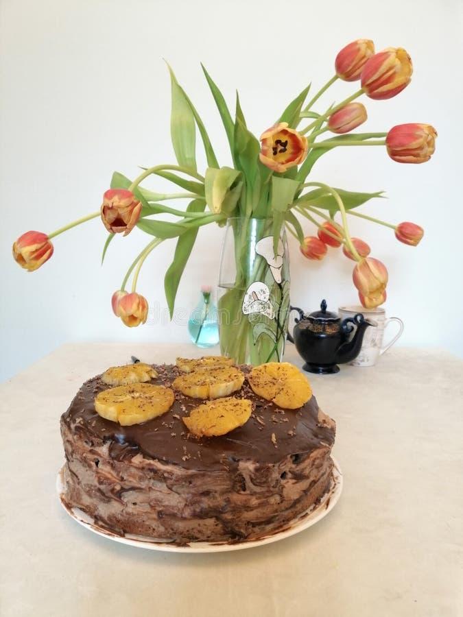 Chokladkaka som dekoreras med apelsiner på bakgrunden av tulpan royaltyfria foton