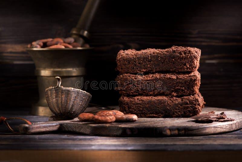 Chokladkaka, stycken av mörk choklad och organiska kakaobönor arkivfoto