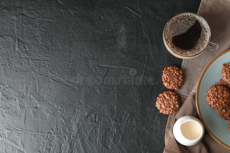 Chokladkakor, kopp kaffe och att mjölka på den svarta tabellen arkivbild