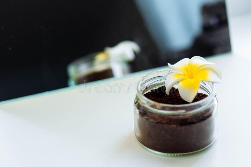 Chokladkokosnötkaffe skurar i en exponeringsglaskrus med en blomma nära spegelnärbildcopyspacen fotografering för bildbyråer
