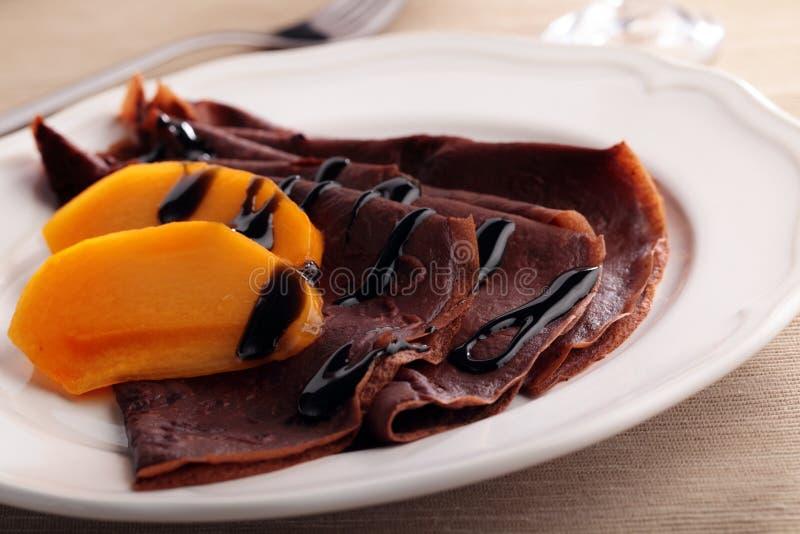 Chokladkräppar med persimonet arkivfoton