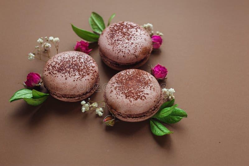 Chokladmacarons med rosor och sidor arkivfoton