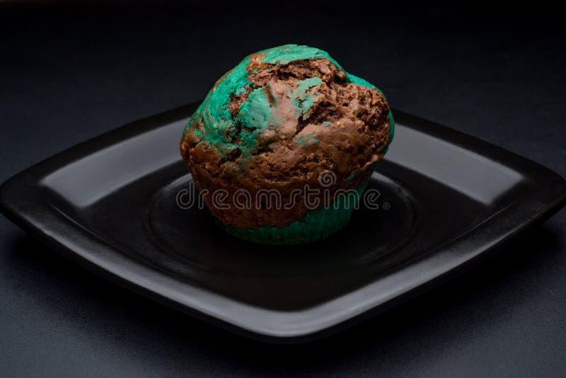 Chokladmintkaramellmuffin på den svarta plattan arkivbild