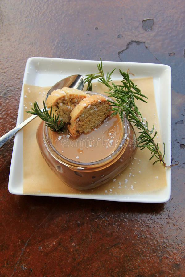 Chokladmousse med salt karamell för hav och kvisten av rosmarin arkivfoton