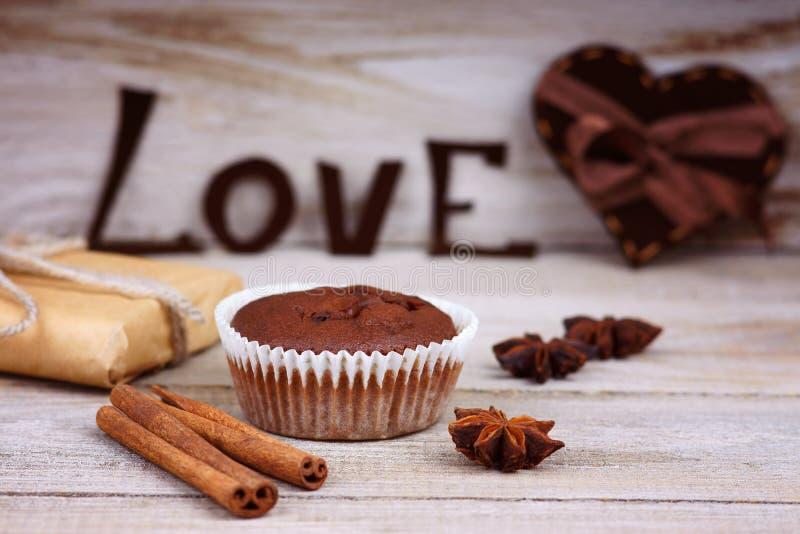 Chokladmuffin, gåvaask, hjärtaform och ordförälskelse arkivbild