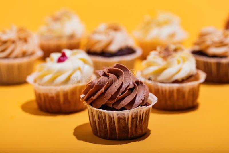 Chokladmuffin i en närbild på gul bakgrund arkivbilder