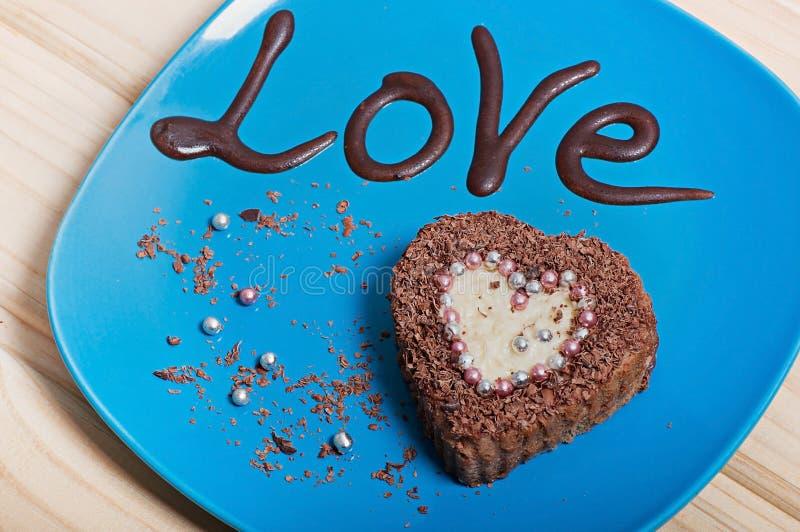 Chokladmuffin i formen av hjärta på en blå platta med inskriftförälskelsen arkivfoto
