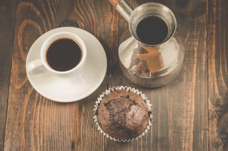chokladmuffin, kaffekopp och turks/chokladmuffin, kaffekopp och turks på en trämörk tabell, bästa sikt arkivfoton