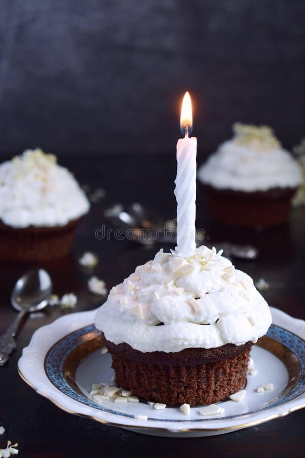 Chokladmuffin med den vaniljkr?m och stearinljuset lycklig f?delsedag M?rkt foto arkivfoto