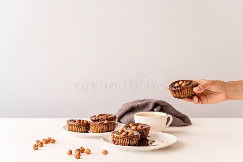 Chokladmuffin med fönsterrutor, valnötter och en kopp kaffe på främre sikt för vit tabell arkivbilder