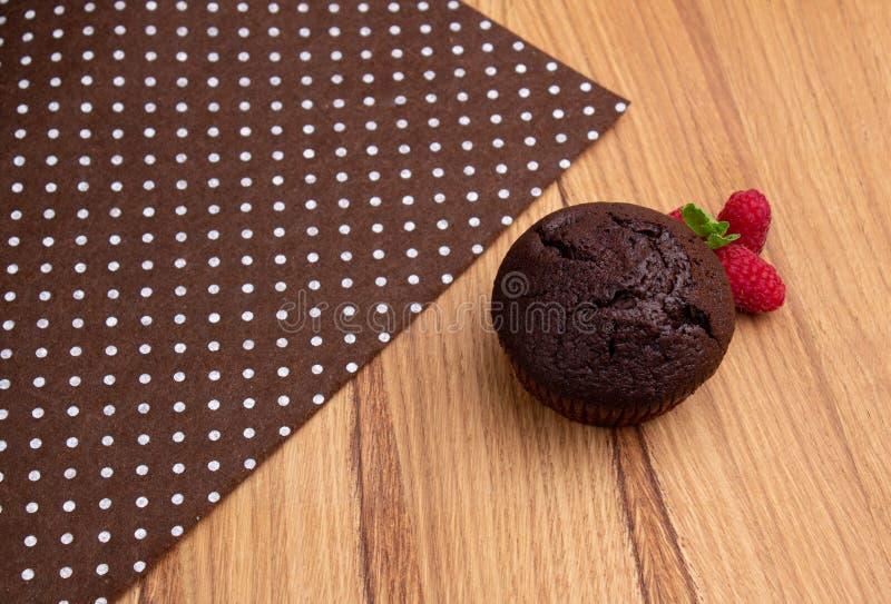 Chokladmuffin med hallonbär på en ljus trätabell royaltyfria foton