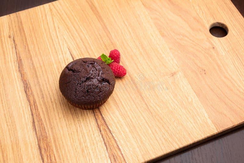 Chokladmuffin med hallonbär på en ljus trätabell fotografering för bildbyråer