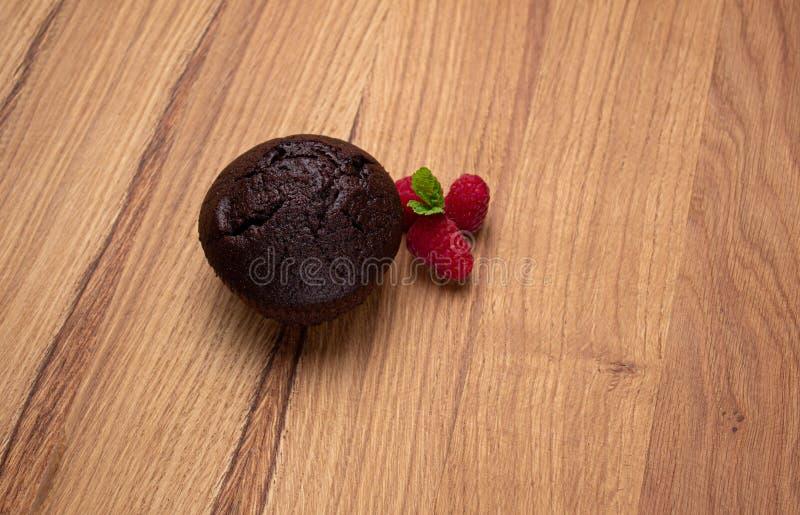 Chokladmuffin med hallonbär på en ljus trätabell arkivfoto