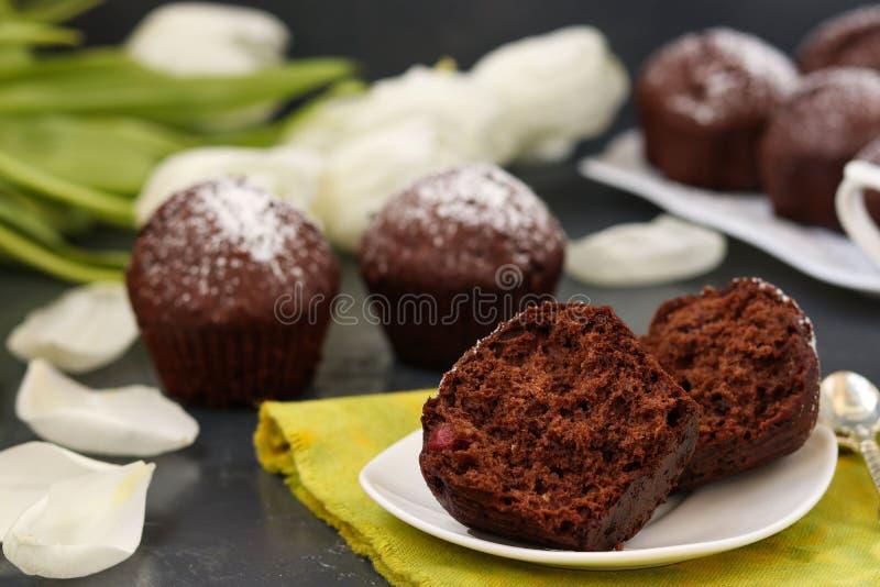 Chokladmuffin med körsbäret som täckas med pulversocker som lokaliseras på en mörk bakgrund arkivbilder