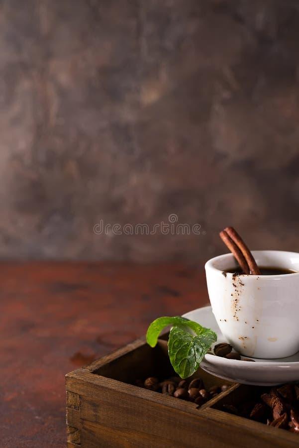 Chokladmuffin med koppen kaffe på en träask med korn av kaffe och kryddor royaltyfri bild