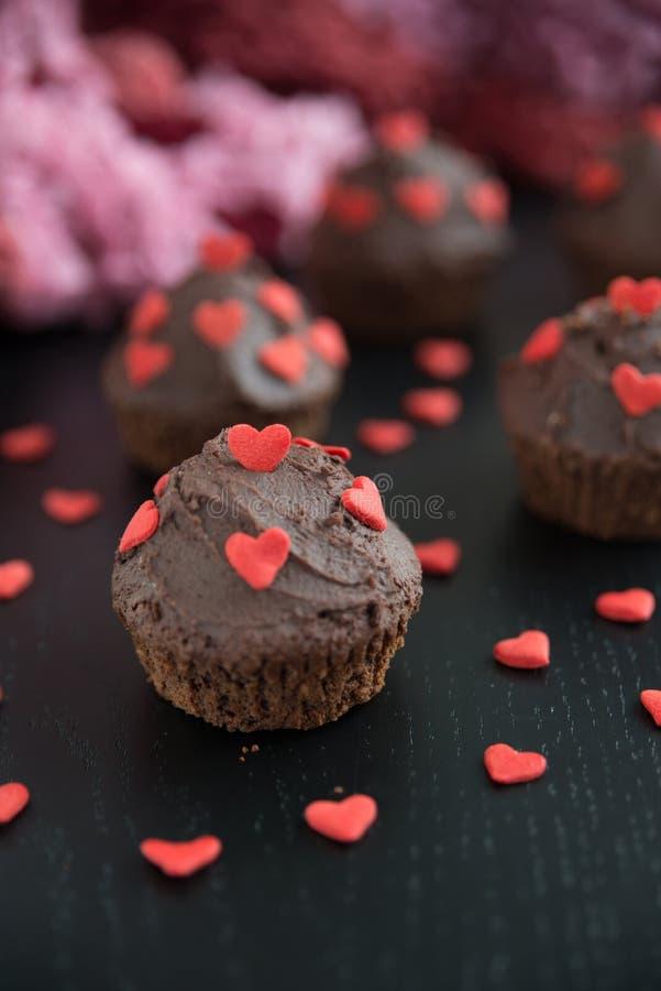 Chokladmuffin med röda sockerhjärtor arkivfoton