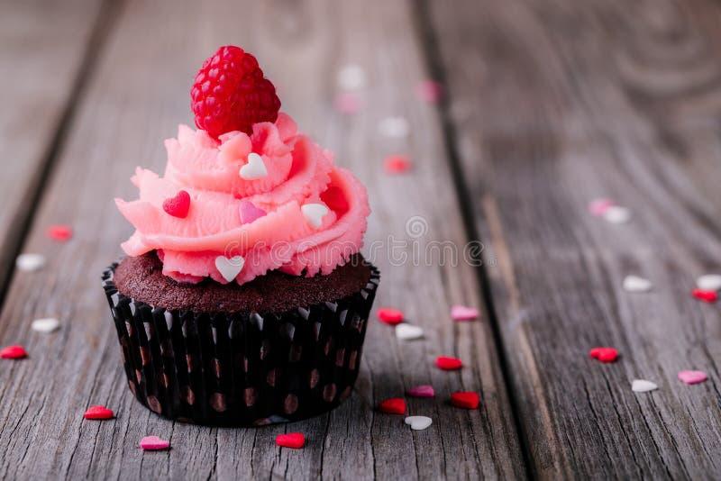 Chokladmuffin med rosa färgkräm, sockerhjärtor och nya hallon för Valentine Day royaltyfri foto
