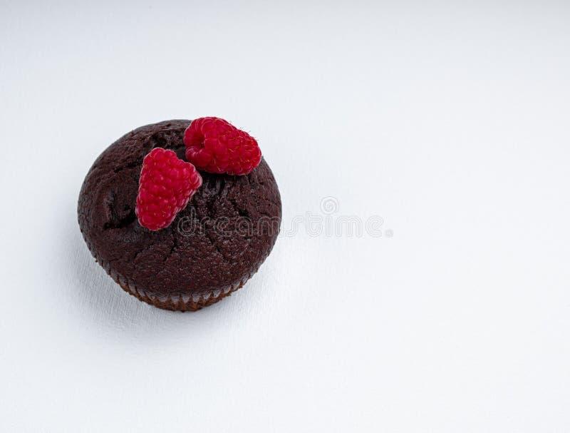 Chokladmuffin med två bär av hallon arkivbilder