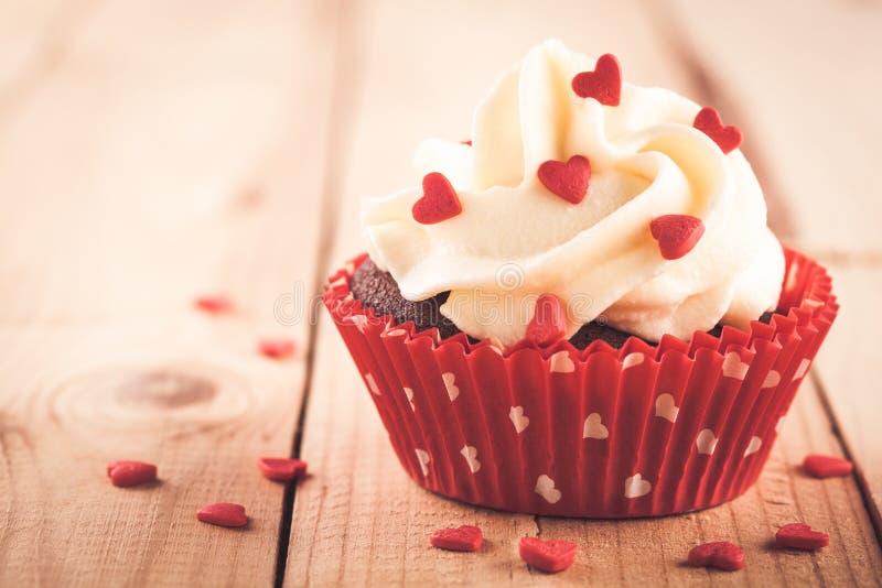 Chokladmuffin med vaniljkräm och röda sockerhjärtor för valentin dag arkivfoto