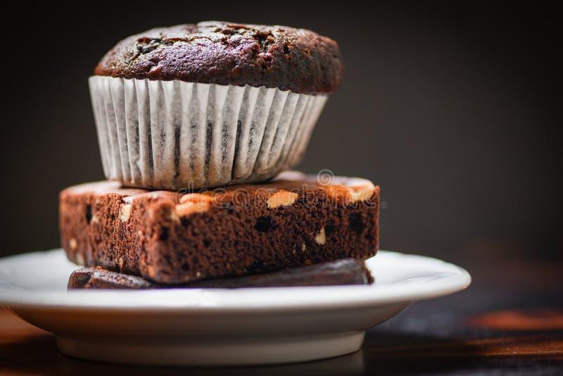 Chokladmuffin på chokladnisset på vit palte med mörker arkivfoton