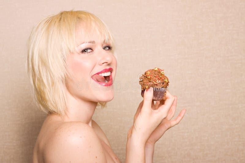chokladmuffin som äter kvinnan arkivfoto