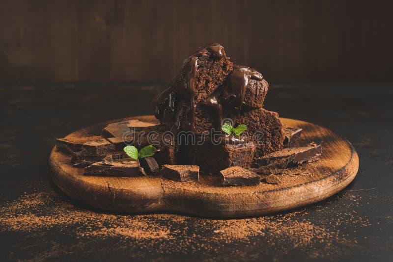 Chokladmuffin som bevattnas med vätskechoklad på en mörk bakgrund royaltyfri bild