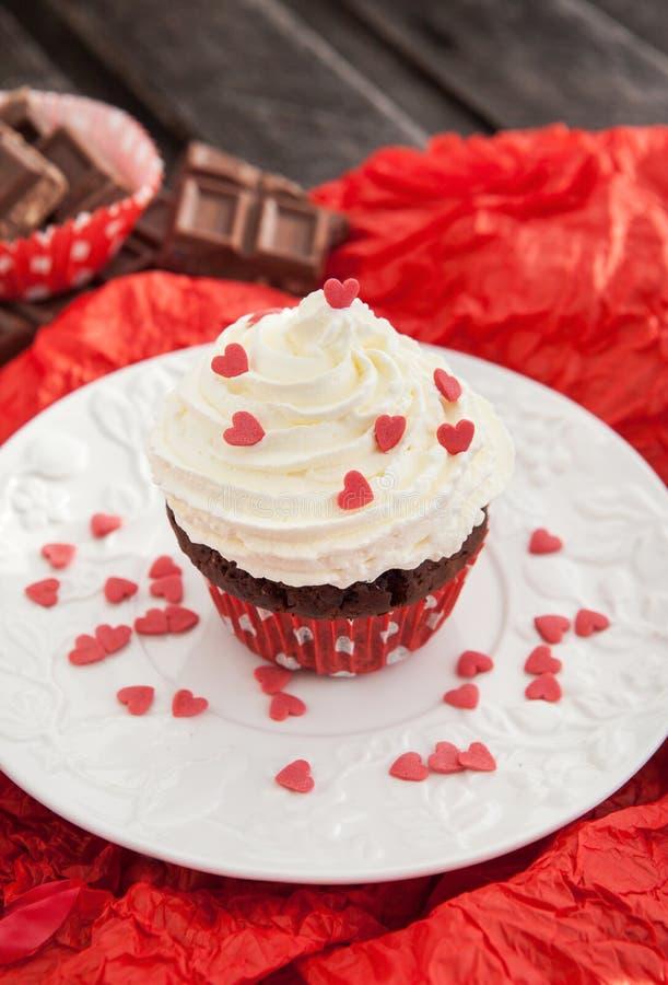 Chokladmuffin som dekoreras med röda hjärtor arkivbild