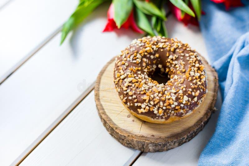 Chokladmunk med röda tulpan på en vit träbakgrund Frukost i sommartid, bästa sikt, kopieringsutrymme royaltyfri fotografi