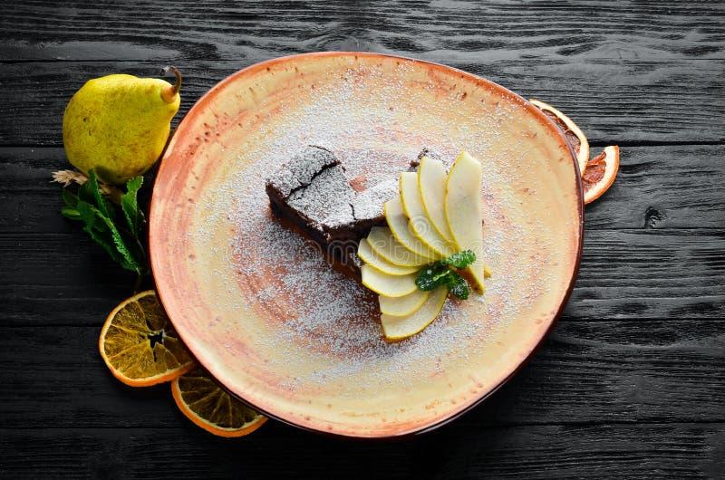 Chokladnisseefterrätt med päronet Efterr?tt bakelse P? en tr?bakgrund arkivfoton