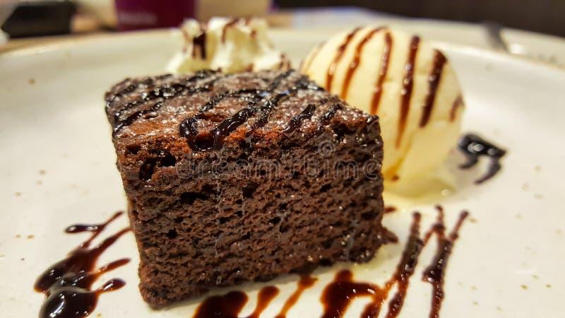 Chokladnissen med glassvanilj på en vit skiva i restaurangen arkivbild