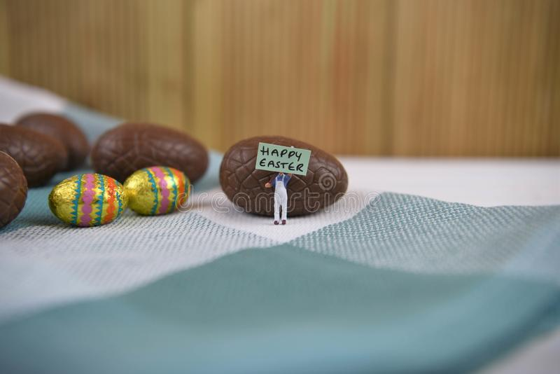 Chokladpåskägg med mini- lycklig påsk undertecknar och ord arkivbilder