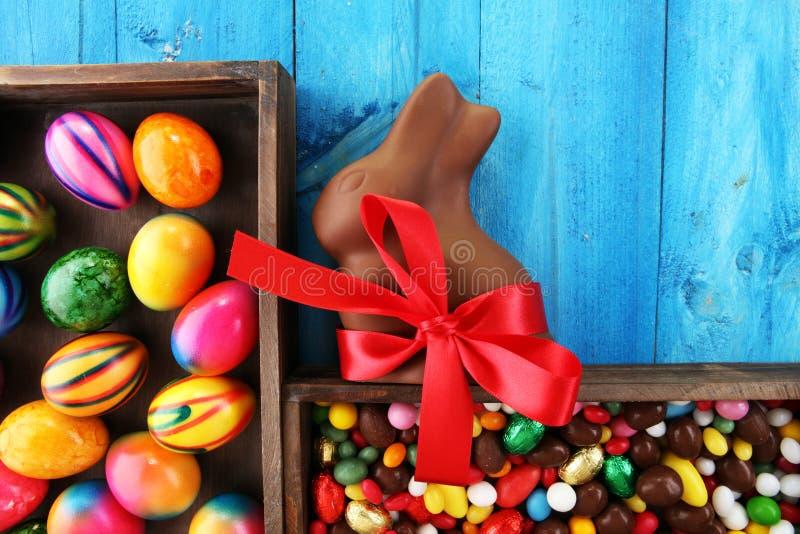 Chokladpåskägg och chokladkanin och färgrika sötsaker royaltyfri bild