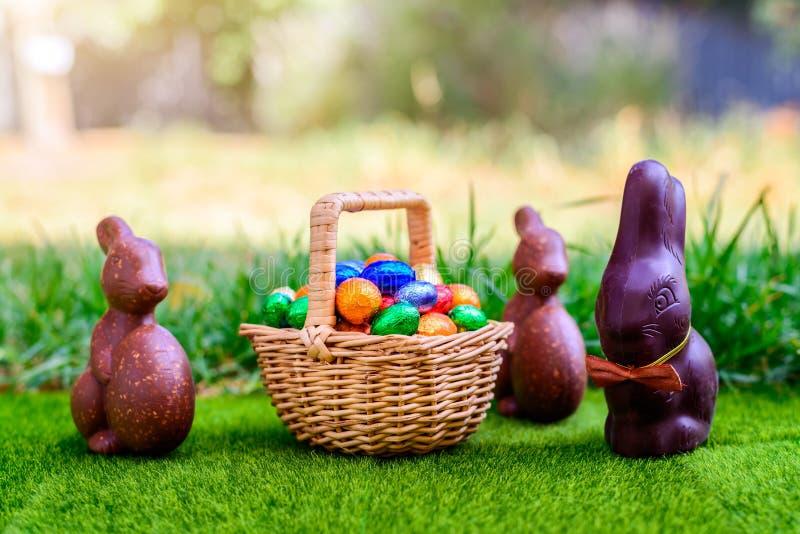 Chokladpåskkanin med korgen mycket av ägg arkivbild