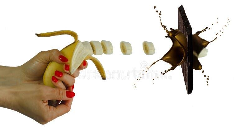 Chokladskytt - banan i hand som en vapenfors en choklad på vit bakgrund royaltyfri bild