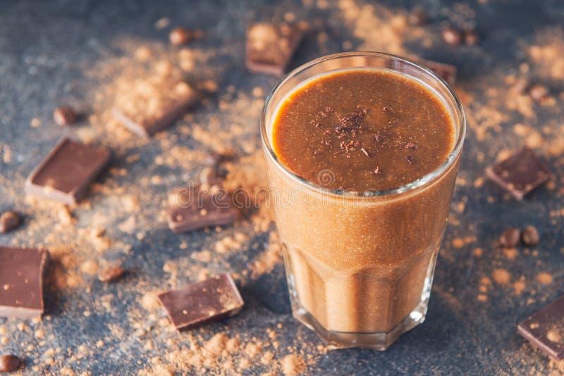 Chokladsmoothie med bananen som dekoreras med chokladchiper på den mörka bakgrunden med stycken av choklad- och kakaopulver H royaltyfria foton