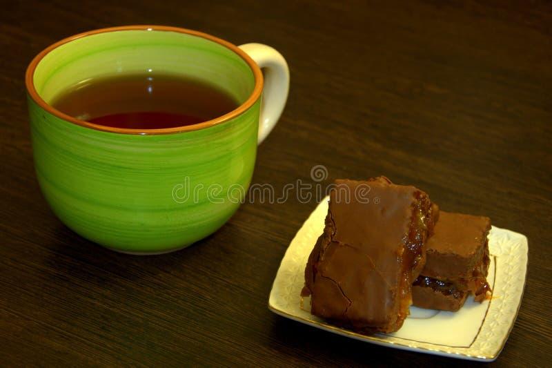 Chokladsockerkaka på en vit porslinplatta och en kopp te arkivbilder
