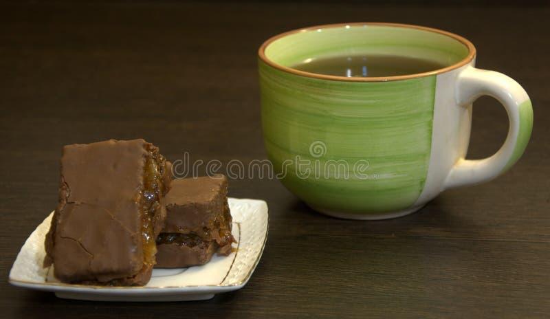 Chokladsockerkaka på en vit porslinplatta och en kopp te royaltyfri bild