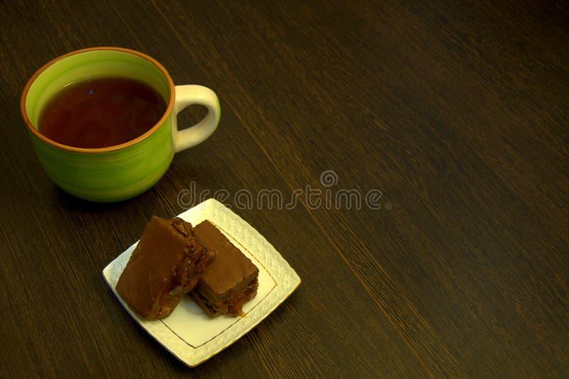Chokladsockerkaka på en vit porslinplatta och en kopp te royaltyfria bilder