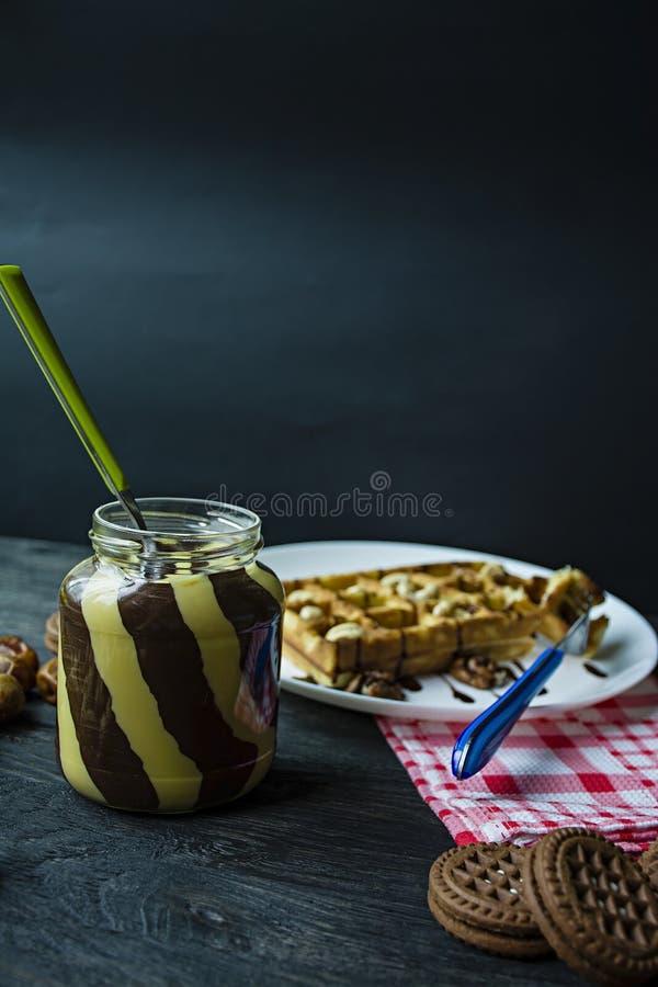 Chokladspridning eller nougatkr?m med hasseln?tter i en exponeringsglaskrus p? en m?rk tr?bakgrund fotografering för bildbyråer