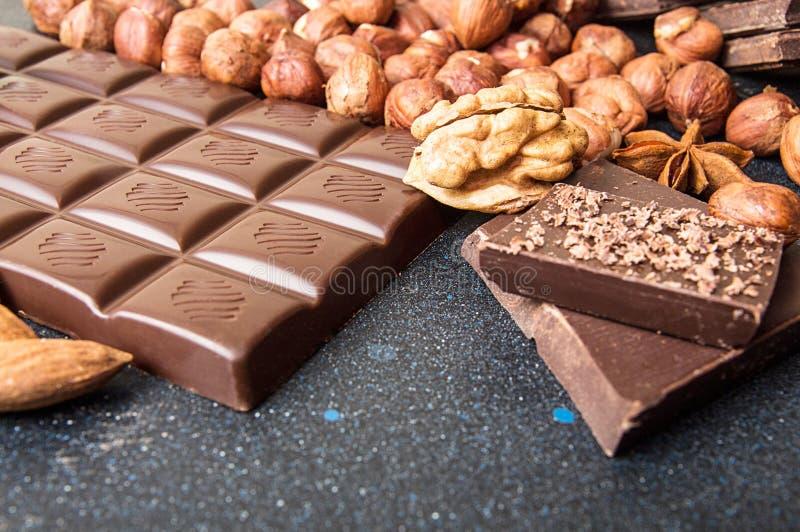 Chokladstycken, filbertsnöt, chokladshavings, valnöt på mörka lodisar arkivfoton